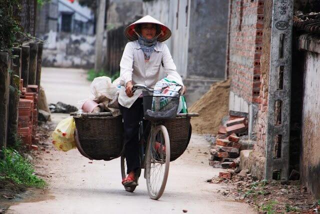 Une femme transporte ses marchandises sur son vélo...