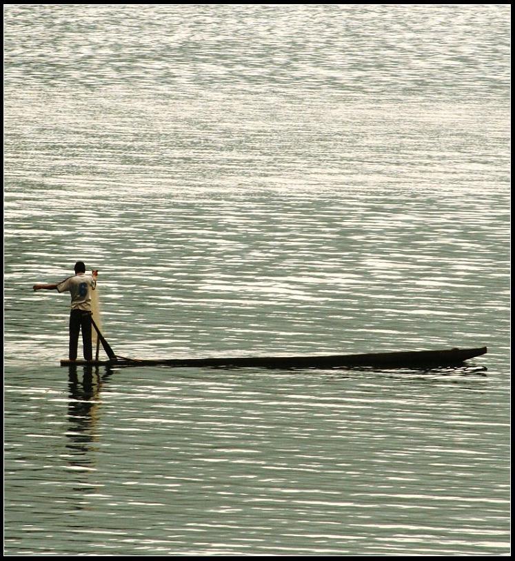 Un pêcheur dépose son filet sur le lac Ba Be